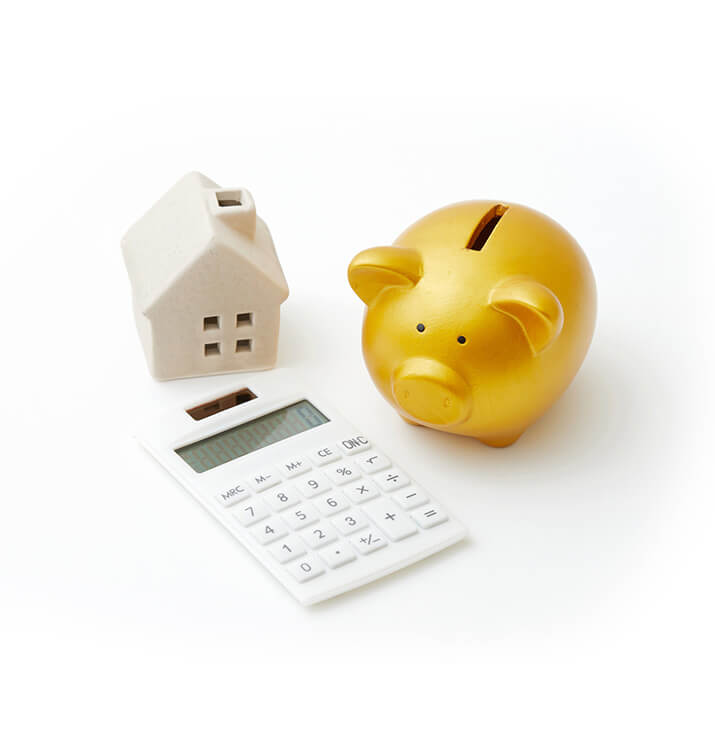 a golden piggy bank with a white calculator next to model sized house